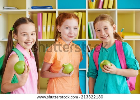 Three charming girls with green apples looking at camera - stock photo
