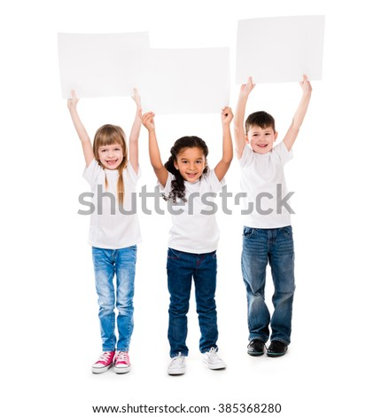 three cheeerful children holding en empty paper sheet above themselves isolated on white background - stock photo