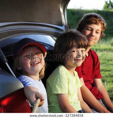 Three cheerful child sitting in the trunk of a car on nature make selfie - stock photo