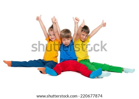 Three cheerful children hold their thumbs up on the white background - stock photo