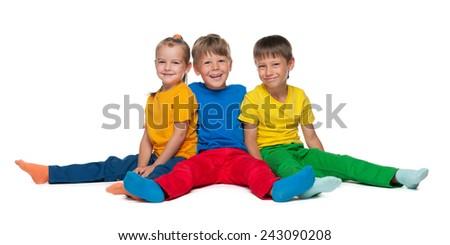 Three cheerful children sit on the white background - stock photo