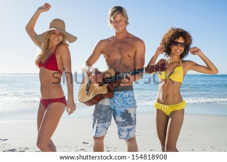 Three cheerful friends having fun on the beach and playing guitar on holidays