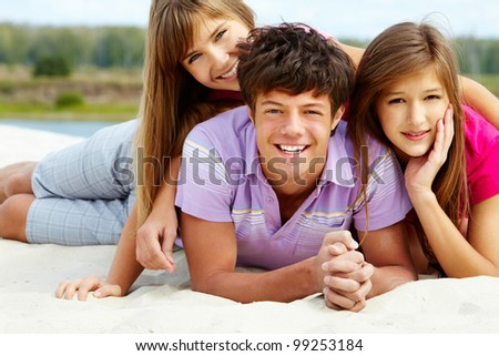 Three cheerful friends spending time together at beach and enjoying warm weather - stock photo