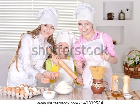 Three cheerful girls cooking in the kitchen together - stock photo