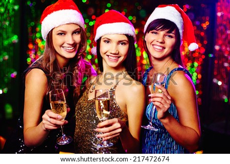 Three cheerful girls in Santa caps toasting at Christmas party