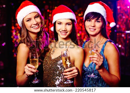 Three cheerful girls in Santa caps wishing you merry Christmas