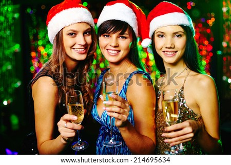 Three cheerful girls looking at camera with smiles at Christmas party - stock photo