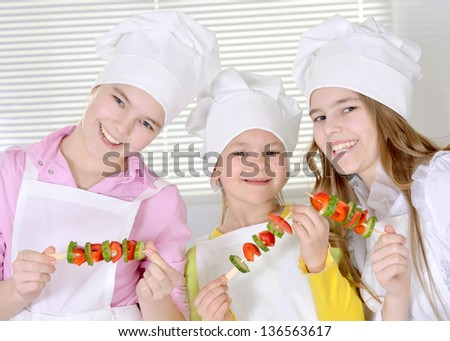 Three cheerful girls preparing dinner in the kitchen at home