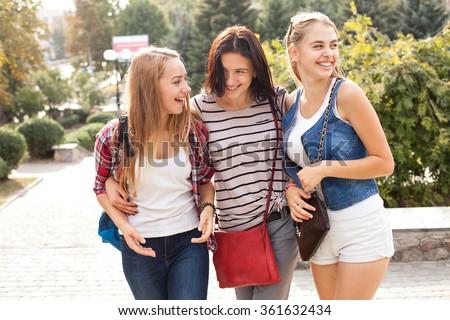 Three cheerful girls walking in the city park - stock photo