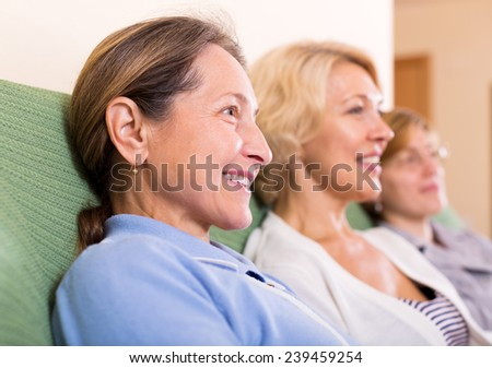three cheerful mature women at home interior sit on the couch - stock photo