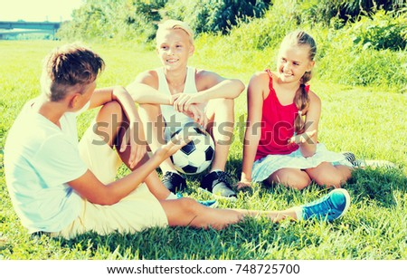 Three cheerful positive smiling kids with ball resting on grass on sunny summer day
