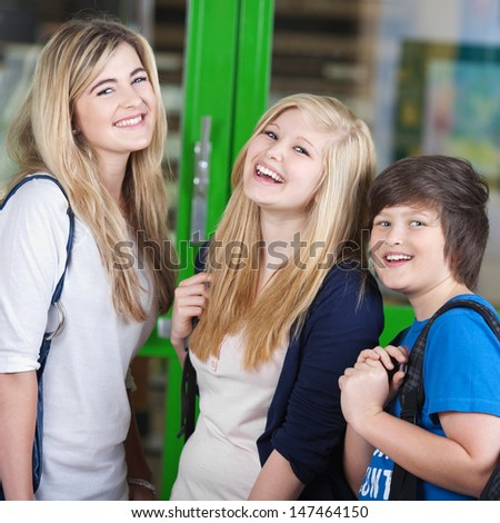Three cheerful young teenage students standing chatting outdoors during a break in their classes, two blond girls and a boy - stock photo