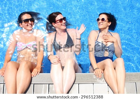 Three cheerful young women simulate that they sit over a pool's edge with a water wall backwards. - stock photo