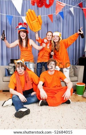 Three cheering women annoying the guys in front who are trying to watch the game on television - stock photo