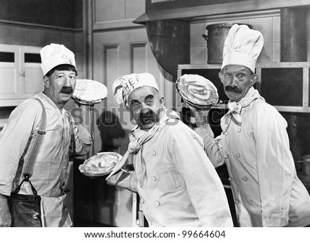 Three chefs holding pies for a fight in the kitchen - stock photo