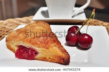 Three cherries and cherry turnover on a white porcelain plate, with a coffee cup in the background. - stock photo