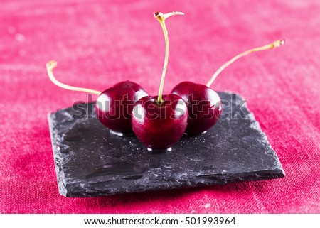 Three cherries over black stone, horizontal image