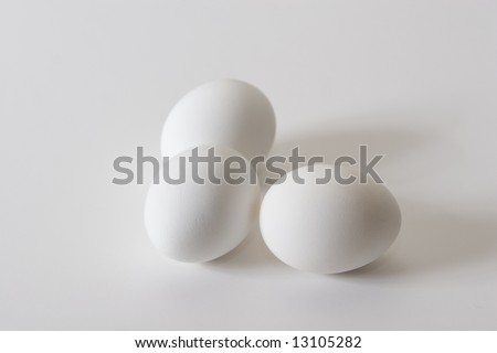 Three chicken eggs on white tabletop with slight shadow off to the right.