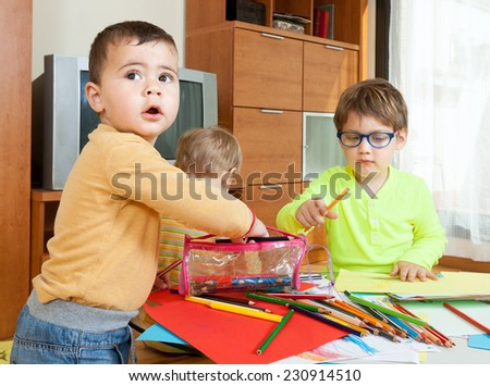 three children at  table with crayons and paper. - stock photo