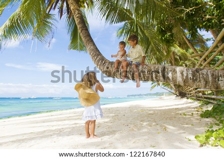 three children - boy and girls - sitting on palm tree on tropical beach background - stock photo