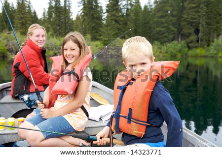Three children fishing together on a lake , focus on the young boy