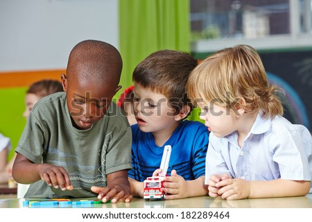 Three children in kindergarten playing with building blocks and cars - stock photo