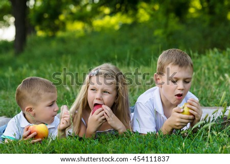 three children lay on the grass