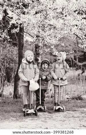 three children on the scooters under the blossom tree - stock photo