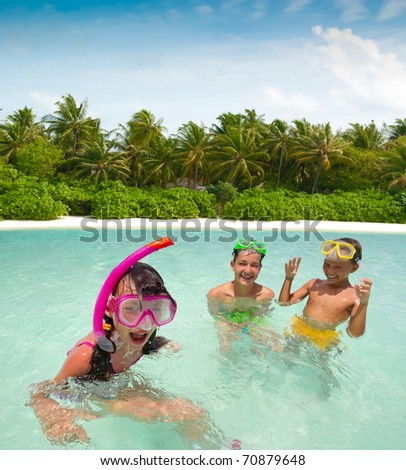Three children playing in the ocean water on Maldives.