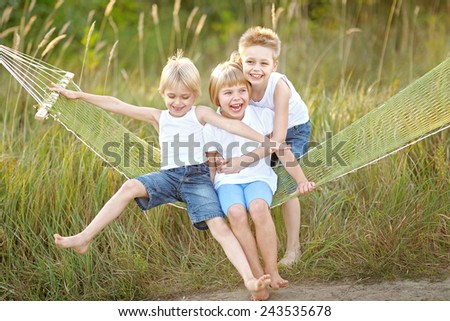 three children playing on meadow in summer - stock photo