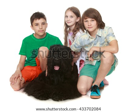 Three children playing with a big black dog-Isolated on white background - stock photo