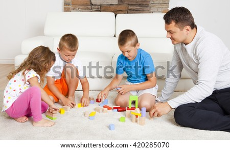 Three children playing with dad with building blocks at home - stock photo