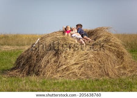 Three children resting in the hay - stock photo