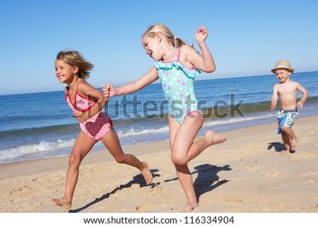 Three Children Running Along Beach - stock photo