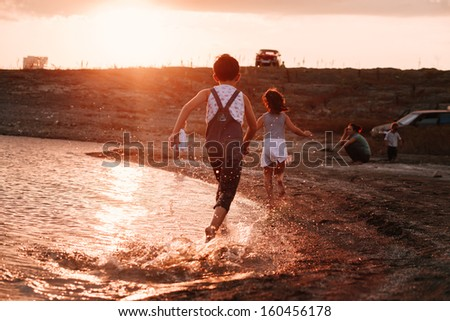 Three Children Running Along Beach - stock photo