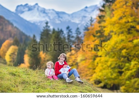 Three children, teenager boy, his toddler sister and a newborn baby brother playing after hiking in beautiful snow covered mountains  - stock photo