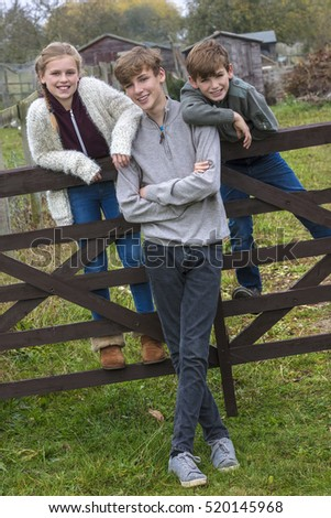 Three children two boys and girl, family brothers and sisters, leaning on a gate in a country garden