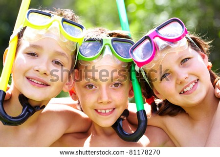 Three children with snorkels looking at camera and smiling