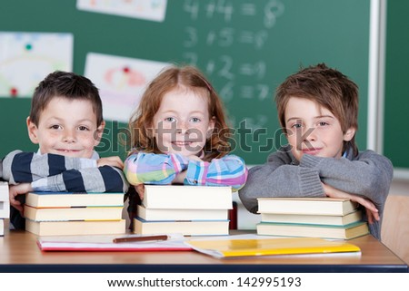 Three children with stack of books inside the classroom