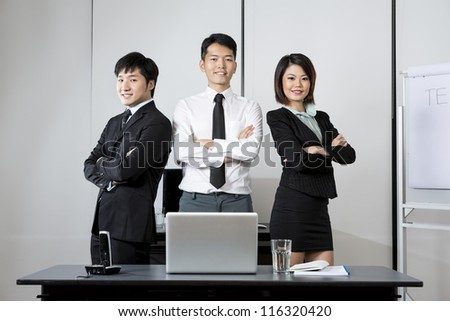 Three Chinese Business colleagues standing in an office.
