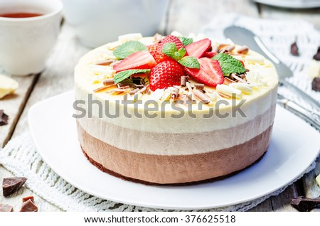 three chocolate cake decorated with strawberries and mint leaves. toning. selective focus - stock photo