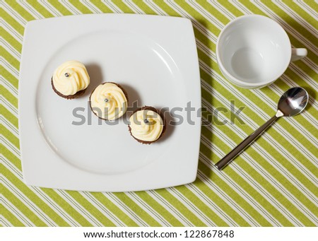 Three chocolate cupcakes with silver sprinkles on top, on white plate and fabric tablecloth with stripes - stock photo