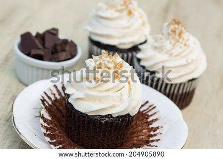 Three chocolate cupcakes with vanilla white icing with one peeled open and chocolate pieces