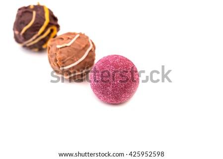 Three chocolate truffles candies pralines on white background, close up - stock photo