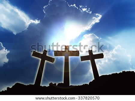 Three christian crosses on the edge of a mountain. Beautiful clouds and halo of light. - stock photo