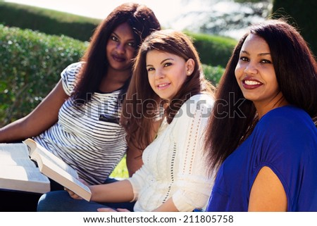 Three Christian girls studying the Bible and looking at the camera - stock photo