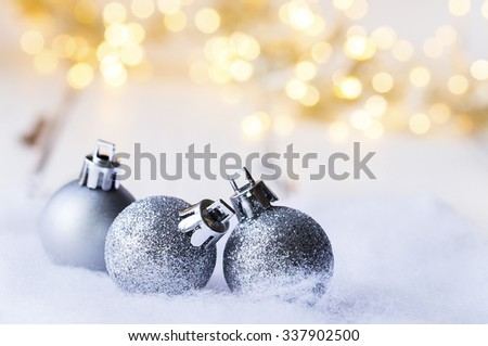 three Christmas ball in silver in front of warm light - stock photo