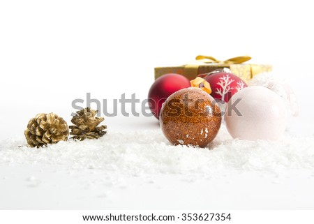 Three Christmas balls in snow on white background
