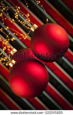 Three Christmas baubles on red and black background