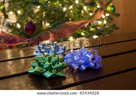 Three Christmas bows sitting on a table in front of a decorated tree